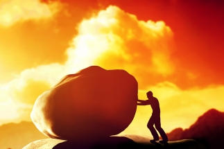 Man pushing a giant, heavy stone, rock over the mountain. Concep